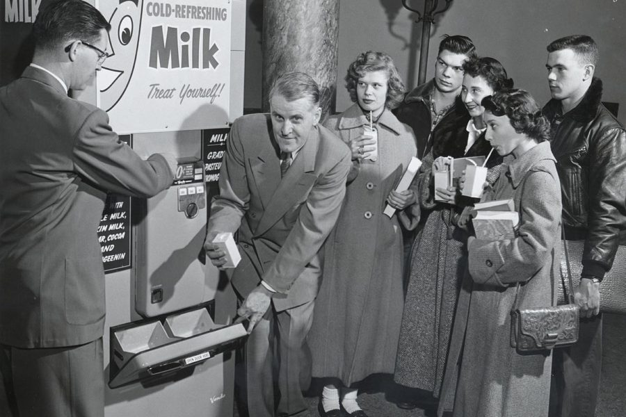 A group of people stand around a milk vending machine in Tripp Hall sipping from containers of milk. The photograph caption indicates that this machine and one in Adams Hall average 300-400 quarts a day. 1955.